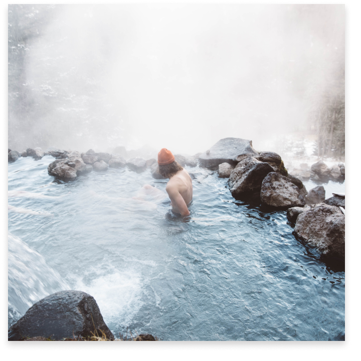 A person in a red beanie sitting in a natural hot spring surrounded by steam.