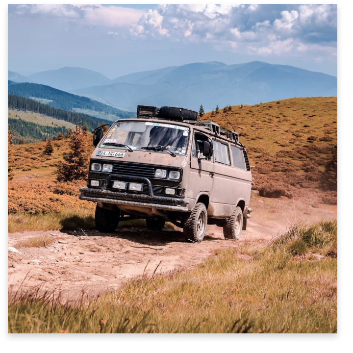 A modded Westfalia van climbs up uneven terrain. Golden hills with trees are in the background