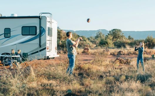 A man and a woman toss a football near an RV.